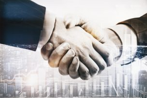 Businessmen shaking hands on abstract city background with business chart. Partnership concept. Double exposure